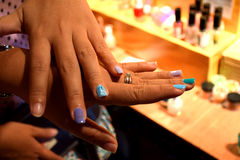The finger to wear a nail polish with the light to fall, it looks pretty smooth again. A young woman show off her fingernail nail polish in a beautiful nail Stock Photo