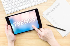 Finger touch screen with Trends word with keyboard and paper on stock photo
