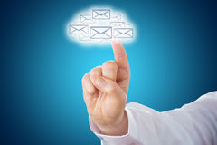 Finger Touching Email Icons Shaping A Cloud Symbol. Index finger pointing at a cloud computing icon shaped out of a host of email letter symbols. The cloud shape Stock Photos