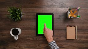 A Finger Touching an i-Pad. A man`s finger touching an i-Pad with a green screen. The i-Pad is on the brown table. View from the top. Close-up Royalty Free Stock Image
