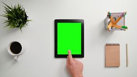 A Finger Touching an i-Pad. A man`s finger touching an i-Pad with a green screen. A tablet is on the white table. View from the top. Close-up Royalty Free Stock Photo