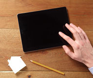 Finger Touching the Screen of an Off Tablet Device Royalty Free Stock Photography