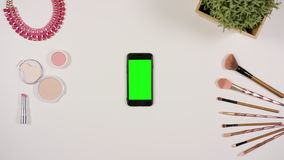 A Finger Touching a Smartphone with a Green Screen. A lady`s finger touching a smartphone with a green screen. The phone is on the white table. View from the top Royalty Free Stock Photo