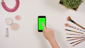 A Finger Touching a Smartphone with a Green Screen. A lady`s finger touching a smartphone with a green screen. The phone is on the white table. View from the top Stock Photo