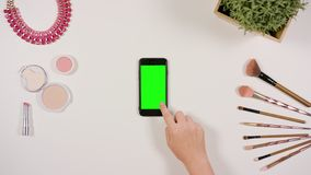 A Finger Touching a Smartphone with a Green Screen. A lady`s finger touching a smartphone with a green screen. The phone is on the white table. View from the top Stock Photos