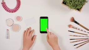 A Finger Touching a Smartphone with a Green Screen. A lady`s finger touching a smartphone with a green screen. The phone is on the white table. View from the top Royalty Free Stock Photography