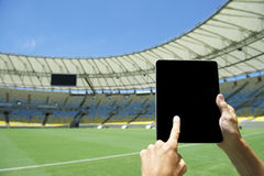 Finger Touching Tablet Football Stadium Rio Brazil. Finger touching blank tablet computer screen in front of soccer field at football stadium Rio de Janeiro Royalty Free Stock Image