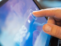 Finger touching tablet-pc. Finger touching screen  on tablet-pc with shallow depth of field Royalty Free Stock Images