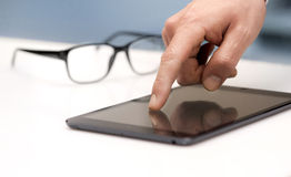 Finger touching a tablet. Selective focus of a male finger touching a tablet with a pair of glasses behind royalty free stock images