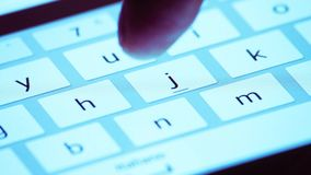 Finger touching virtual keys form a digital keyboard of a touchscreen tablet device stock footage