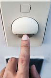 A finger is turning on a light switch. Royalty Free Stock Photography