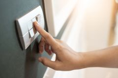 Finger is turning on or off on light switch. Close up of Female finger is turning on or off on light switch over green wall covering. Copy space royalty free stock photo