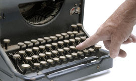 Finger on a type writer key Stock Photos