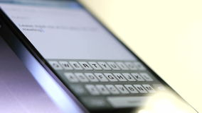 Finger typing out a text message on a phone. Text messaging in a cellphone stock video footage