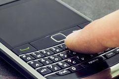 Finger typing on smartphone Stock Photography