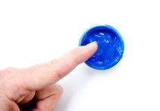Finger und blaue Farbfarbe in einem Glas auf weißem Hintergrund Stockbilder