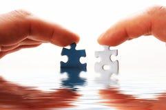 Finger und Puzzlespiel im Wasser Stockbilder