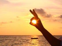 Finger und Sonne mustern auf dem Sonnenunterganghintergrund Stockbilder
