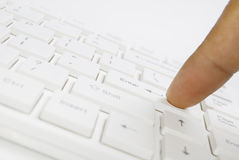Finger on white computer keyboard Royalty Free Stock Photo