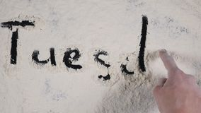 Finger write TUESDAY on a white flour background. top view 4k.  stock footage