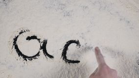Finger write on a white flour background. top view 4k.  stock footage