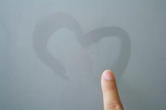 Finger written heart on frosted glass Royalty Free Stock Photos
