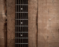 Fingerboard from the acoustic guitar on wooden background Royalty Free Stock Image