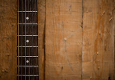Fingerboard from the acoustic guitar on wooden background Stock Photos