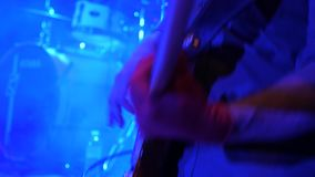 Fingerboard of electric guitar with fingers of virtuoso at concert. Musician with guitar at stage closeup. Virtuoso stock footage