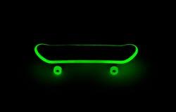 Fingerboard glowing in the dark. Green glow of a fingerboard in the dark royalty free stock image