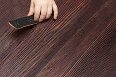 Fingerboard on wooden background in hands of the baby Stock Image
