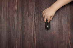 Fingerboard on wooden background in hands of the baby Royalty Free Stock Photos