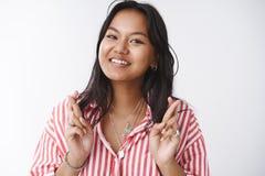 Fingeres cruzados del estudiante vietnamita optimista para la buena suerte y la anticipación sonriente para las noticias y los re fotos de archivo libres de regalías