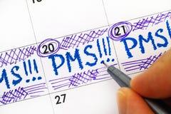 Fingeres de la mujer con el recordatorio PMS de la escritura de la pluma en calendario Foto de archivo
