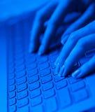 Fingeres de la mujer en el teclado del ordenador portátil en tonos azules Fotografía de archivo