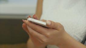 Fingeres de la mujer que mandan un SMS a mensajes usando el teléfono celular almacen de metraje de vídeo
