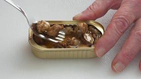 Fingeres de Man's que sostienen la lata mientras que come conchas de peregrino ahumadas almacen de metraje de vídeo