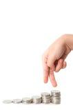 Fingeres del niño que caminan abajo en las pilas de monedas de plata Foto de archivo libre de regalías