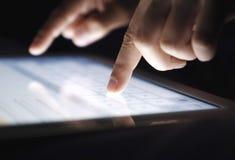Fingeres del primer que mecanografían mandando un SMS a un mensaje en la tableta fotos de archivo libres de regalías