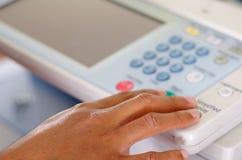 Fingeres del primer que presionan los botones de la exhibición en la fotocopiadora Fotografía de archivo