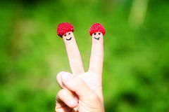 Fingeres felices de los pares con las frambuesas y las sonrisas pintadas imágenes de archivo libres de regalías