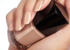 Fingeres femeninos hermosos con la manicura beige brillante del naturel ideal que sostiene la botella del esmalte de uñas Cuidado Foto de archivo