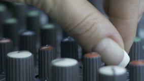 Fingeres femeninos que dan vuelta a botones del equalizador en mezclador almacen de video