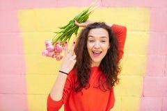 Fingeres hermosos de la demostración dos de la muchacha sobre fondo colorido Imagenes de archivo