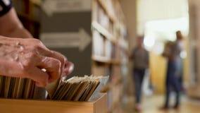 Fingeres humanos en catálogo de tarjetas en la biblioteca almacen de video