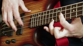 Fingeres masculinos del cierre-u que juegan a solas en la guitarra baja almacen de video