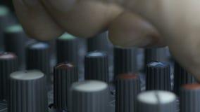 Fingeres masculinos que dan vuelta a botones del equalizador en mezclador almacen de metraje de vídeo