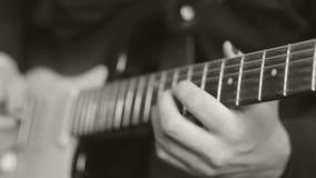 Fingeres masculinos que juegan en la guitarra eléctrica, blanco y negro almacen de metraje de vídeo
