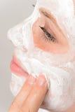 Fingeres que aplican a la chica joven de la crema hidratante de la mascarilla Foto de archivo