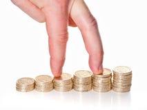 Fingeres que caminan para arriba en pilas de monedas de una libra Fotos de archivo libres de regalías